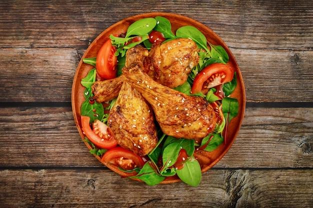 소박한 나무 배경에 샐러드와 구운 된 치킨 나지만 닫습니다. 평면도. 프리미엄 사진