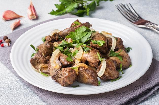 Baked chicken liver with onion on a plate. Premium Photo
