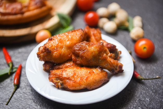 Baked chicken wing bbq grill on plate, hot and spicy chicken and sauce on dark Premium Photo