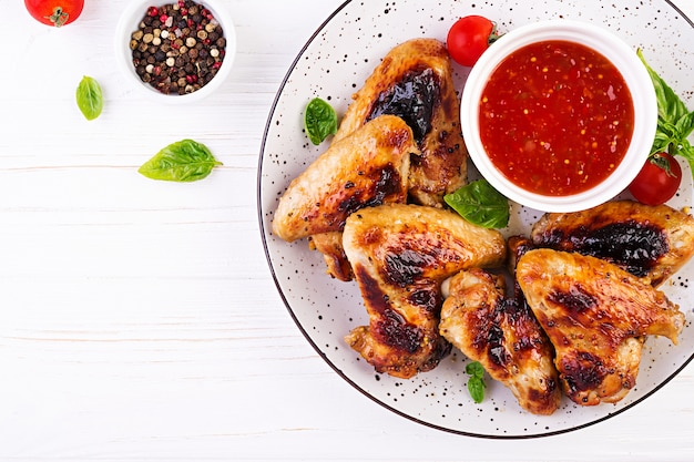 Baked chicken wings in the asian style and tomatoes sauce on plate Free Photo