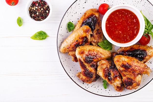Ali di pollo al forno in stile asiatico e salsa di pomodori sul piatto Foto Gratuite