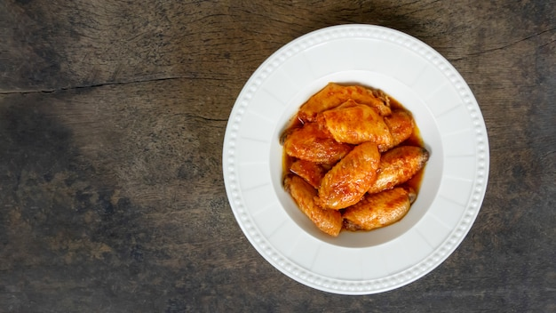Baked chicken wings  on dish over wooden background Premium Photo
