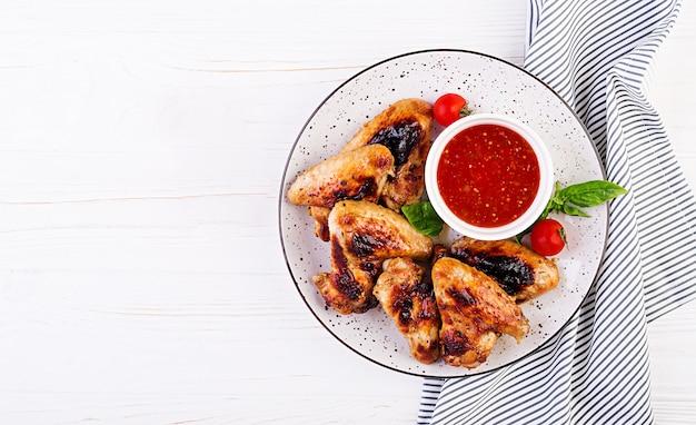 접시에 토마토 소스와 아시아 스타일의 구운 닭 날개 무료 사진