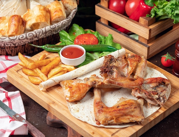Baked chicken wings with french fries in lavash with vegetables and ketchup on wooden board Free Photo