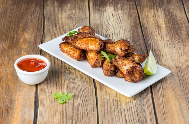 Baked chicken wings with lime and tomato sauce Premium Photo
