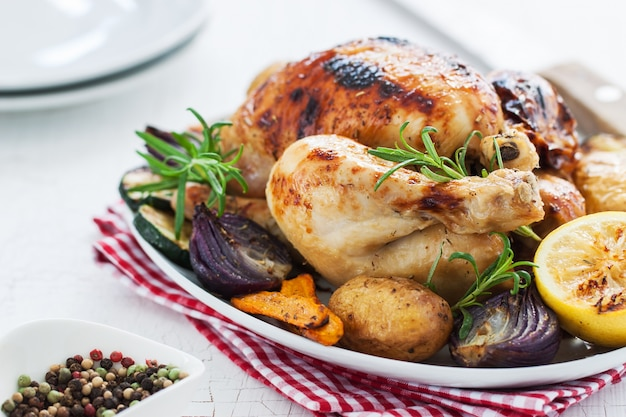 Baked chicken with lemon and vegetables in a dish Free Photo