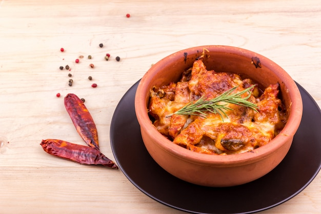 Baked chicken with mushrooms and cheese in a clay pot Premium Photo