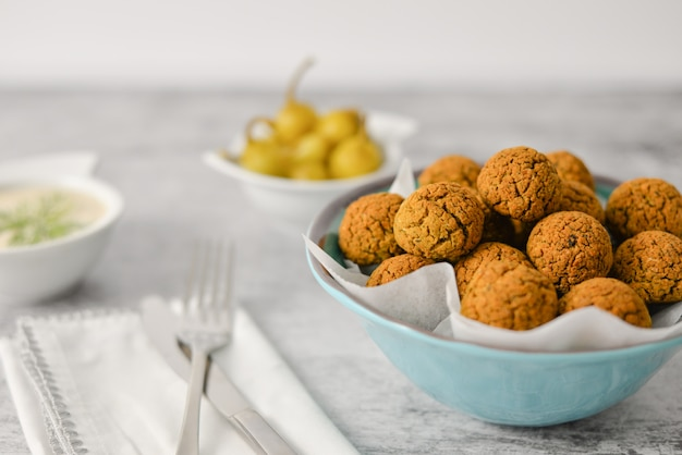 Baked chickpea falafel balls on blue plate on grey , healthy and vegan food with tahini deep and hot pepper , traditional mediterranean , top view , flat lay with copy space Premium Photo