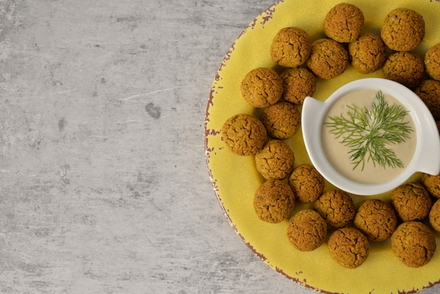 Baked chickpea falafel balls on yellow plate on grey , healthy and vegan food with tahini deep , traditional mediterranean , top view , flat lay with copy space Premium Photo