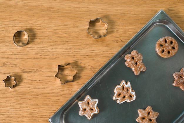 Baked christmas cookies and pastry cutters on wooden table Free Photo