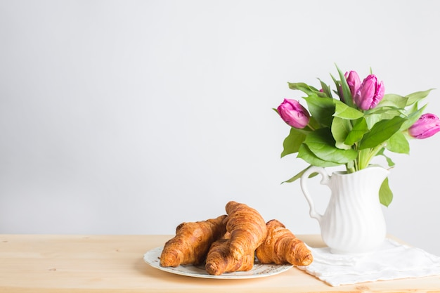 Baked croissants plate near the vase on wooden desk isolated on white background Free Photo