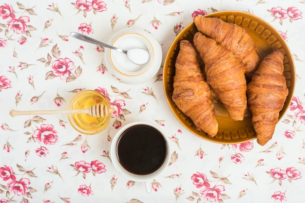 Baked croissants; tea; honey and powdered milk on floral background Free Photo