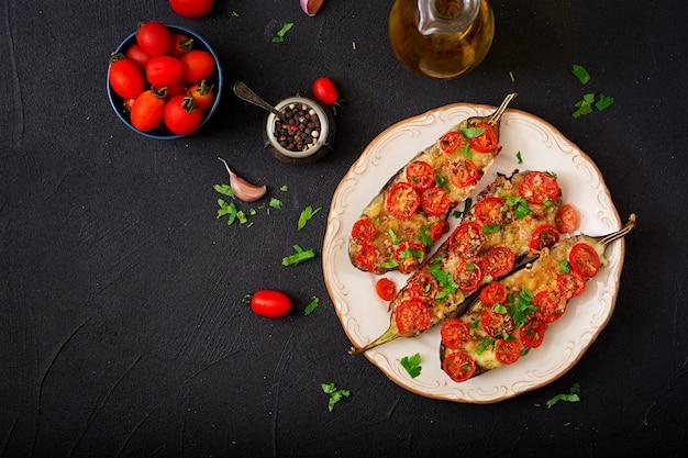 Baked eggplants with mozzarella and tomatoes with italian herbs. Premium Photo