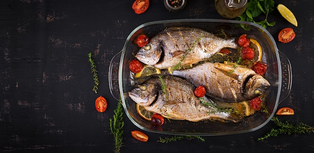 Baked fish dorado with lemon and herbs in baking pan Free Photo