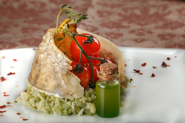 Baked fish on a vegetable side dish with cherry tomatoes. Premium Photo