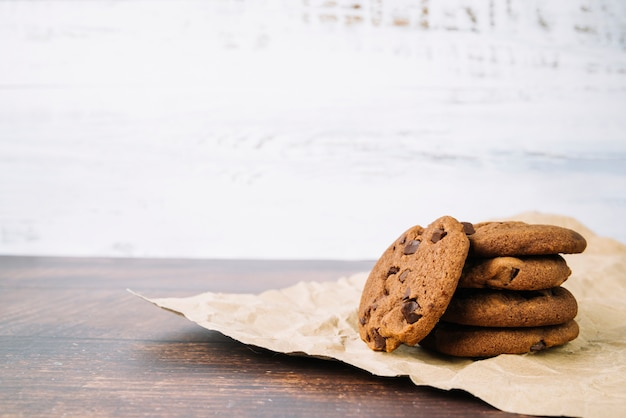 Baked fresh chocolate cookies on brown paper on wooden table Free Photo