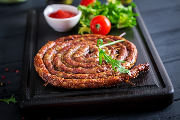Baked homemade sausage on a wooden board. Free Photo