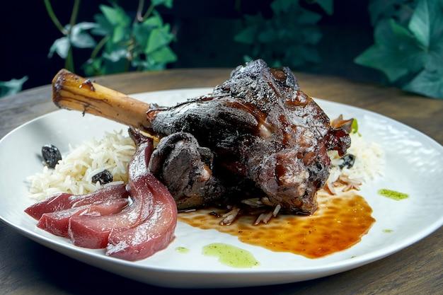 Запеченная рулька ягненка с рисом и грушей в белой тарелке на деревянной поверхности. Premium Фотографии