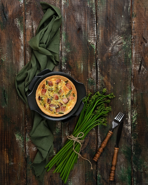 Baked lauren quiche with bacon and young bracken shoots Premium Photo