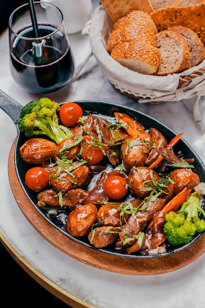Baked meat with vegetables on a wooden stand Free Photo