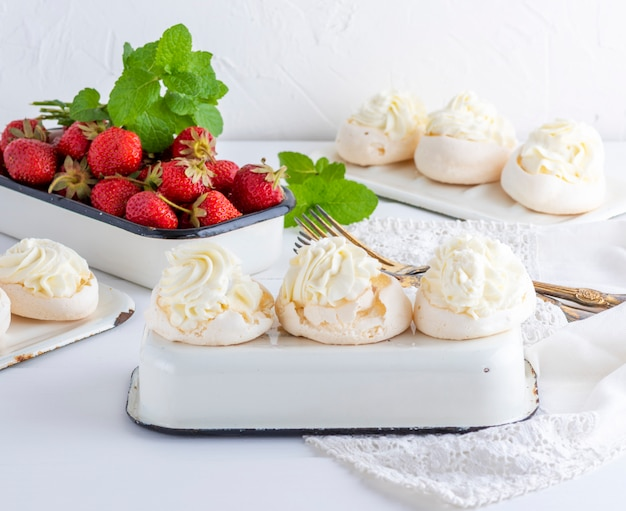 Baked meringue with cream and fresh strawberries Premium Photo