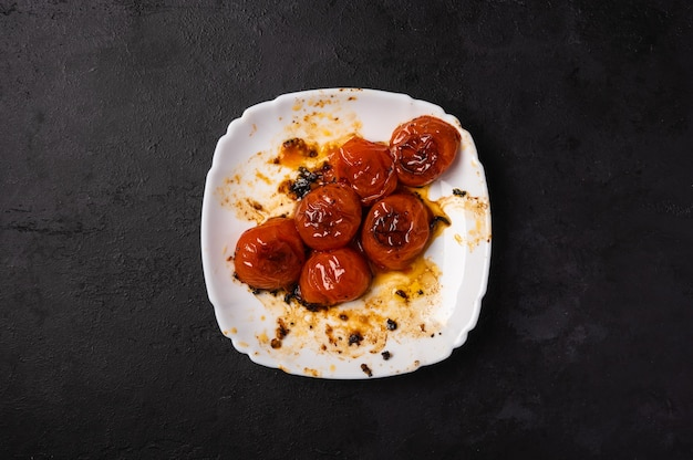 Baked minted cherry tomatoes on a white plate with traces of oil on a dark background, copy space Premium Photo