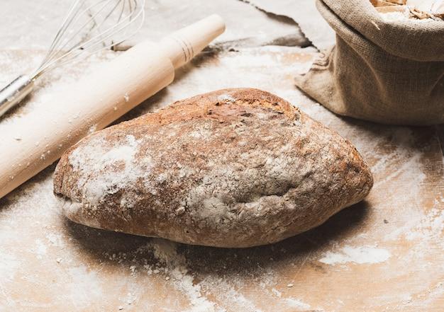 Запеченный овальный хлеб из ржаной муки на металлическом противне на столе, вид сверху Premium Фотографии