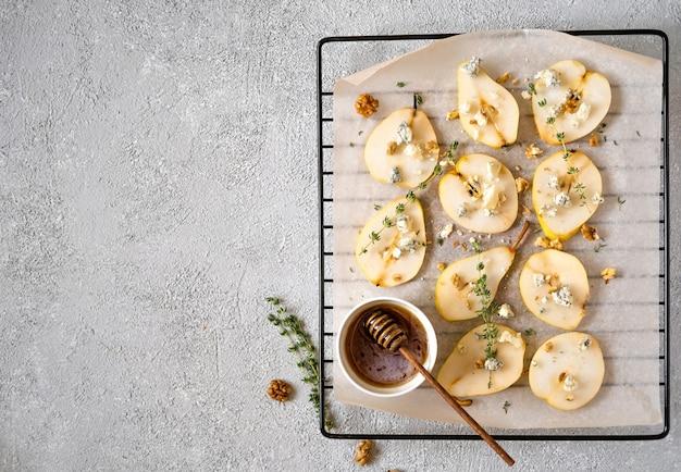 Запеченные груши с голубым сыром, грецкими орехами, медом и зеленью. Premium Фотографии