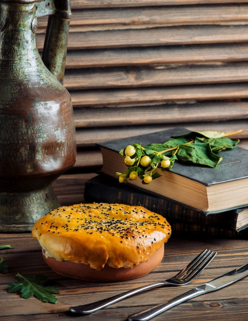 Baked pie stuffed with food inside a pottery bowl Free Photo