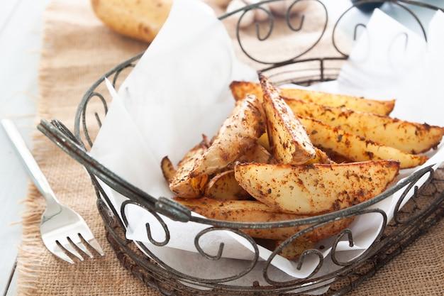 Baked potato wedges on basket - homemade organic vegetable, vegan potato wedges snack food meal Premium Photo