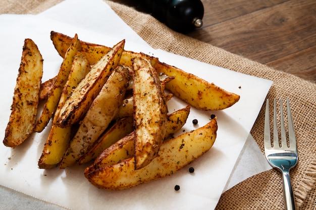 Baked potato wedges - homemade organic vegetable, vegan potato wedges snack Premium Photo
