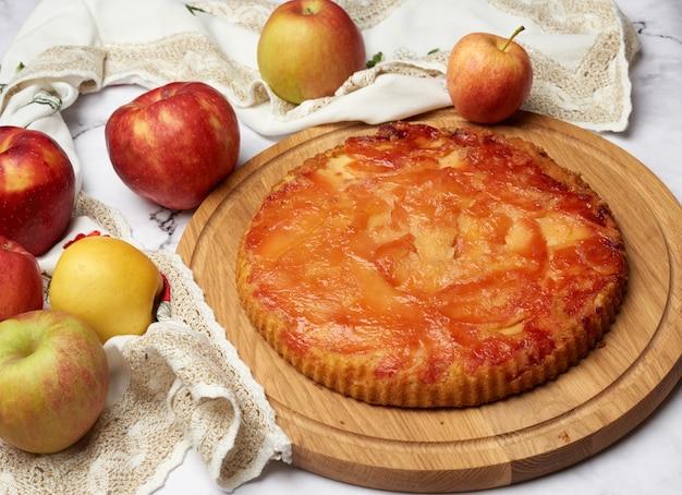 Запеченный круглый яблочный пирог на деревянной доске Premium Фотографии