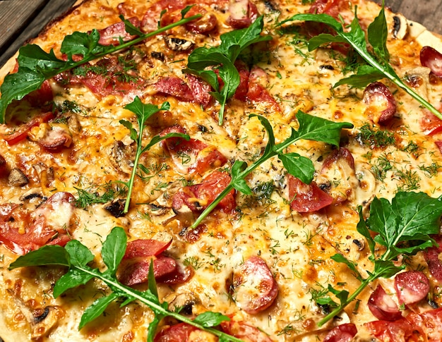 Baked round pizza with smoked sausages, mushrooms, tomatoes, cheese and arugula leaves Premium Photo