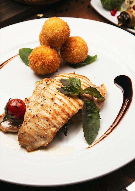 Baked salmon fillet with potatoes and cheese rolls, and vegetables mix. Free Photo