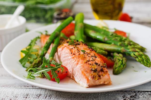 Запеченный лосось с гарниром из спаржи и помидоров с зеленью Бесплатные Фотографии