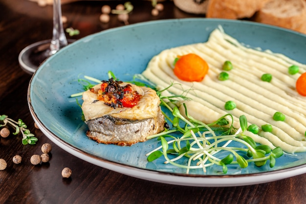Baked sea bass fish with vegetables and mashed potatoes Premium Photo