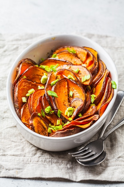 Baked sliced sweet potato with green onions in white dish. Premium Photo