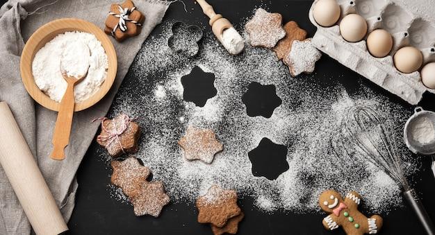 Запеченное имбирное печенье в форме звезды, посыпанное сахарной пудрой, на черном столе и ингредиенты, вид сверху Premium Фотографии