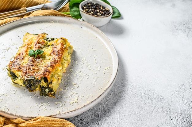Запеченная фаршированная вегетарианская паста каннеллони с брокколи, шпинатом, базиликом и сыром. серый фон вид сверху. копировать пространство Premium Фотографии
