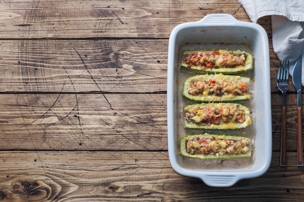 Baked stuffed zucchini boats with minced chicken mushrooms and vegetables with cheese on a baking sheet. top view copyspace Premium Photo
