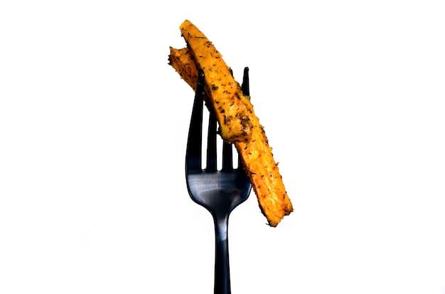 Запеченный сладкий картофель на черной вилке Premium Фотографии