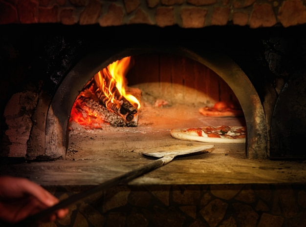 Baked tasty margherita pizza getting out of the oven Premium Photo