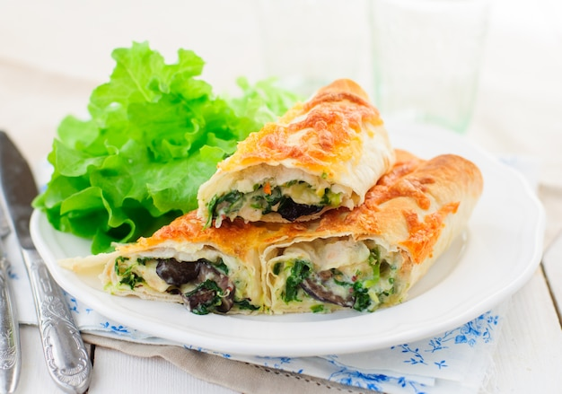 Baked tortilla rolls with spinach, chicken and mushrooms Premium Photo