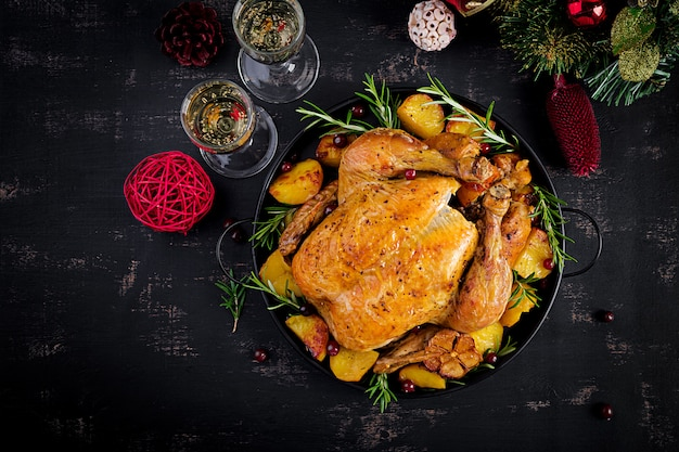 Baked turkey or chicken. the christmas table is served with a turkey, decorated with bright tinsel. fried chicken. table setting. christmas dinner. top view Premium Photo