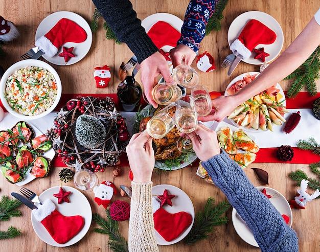 Tacchino al forno. cena di natale. la tavola di natale è servita con un tacchino, decorato con orpelli luminosi e candele. pollo fritto, tavola. cena di famiglia. vista dall'alto, mani nel telaio Foto Gratuite