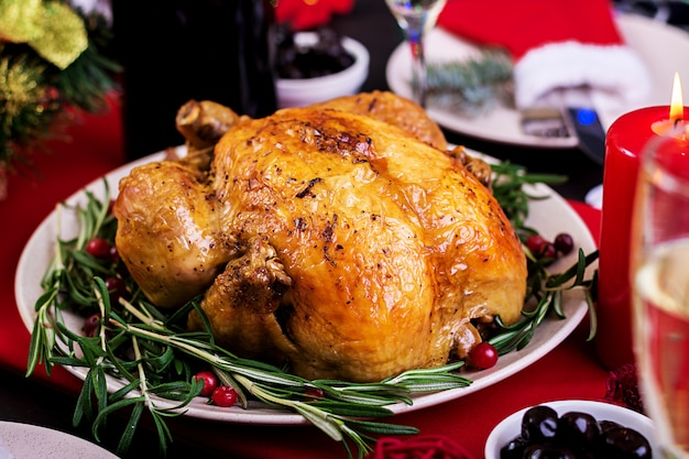 Baked turkey. christmas dinner. the christmas table is served with a turkey, decorated with bright tinsel and candles. fried chicken, table.  family dinner. Free Photo