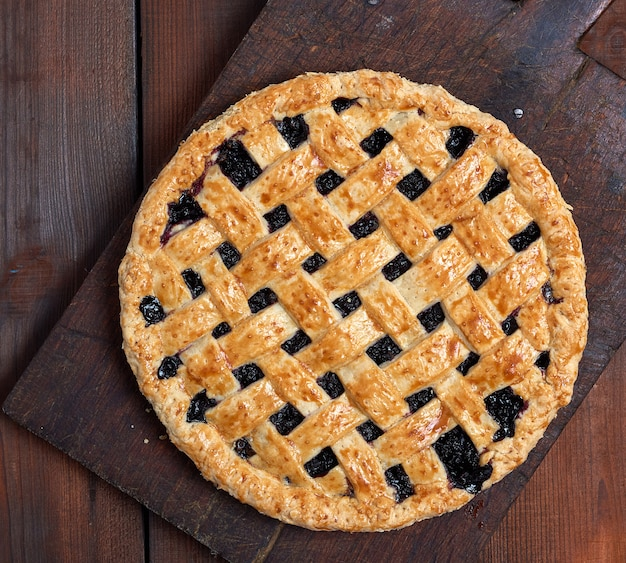 Baked whole black currant pie lay on a brown wooden cutting board Premium Photo