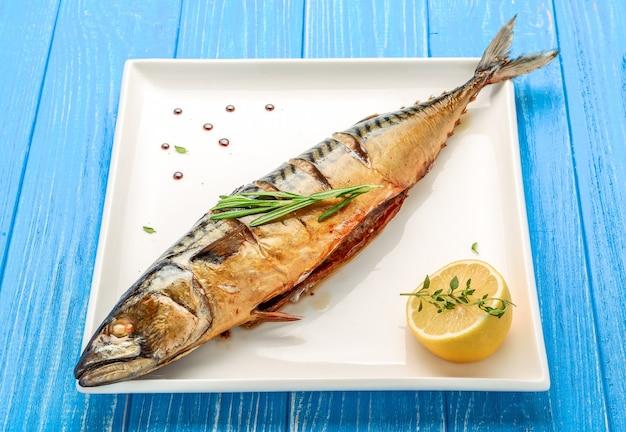 Запеченная целая рыба на гриле на тарелке с овощами и лимоном Premium Фотографии