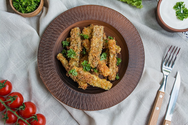 Baked zucchini with cheese and breadcrumbs. vegan food. vegetarian cuisine. view from above. light background. Premium Photo