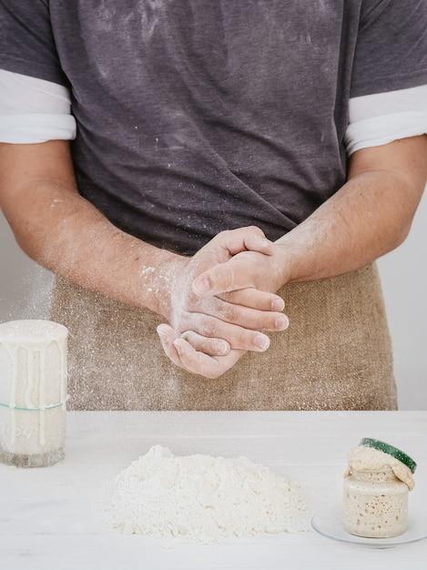 ベイカーはキッチンで小麦粉で手をたたき、焼く準備ができました 無料写真